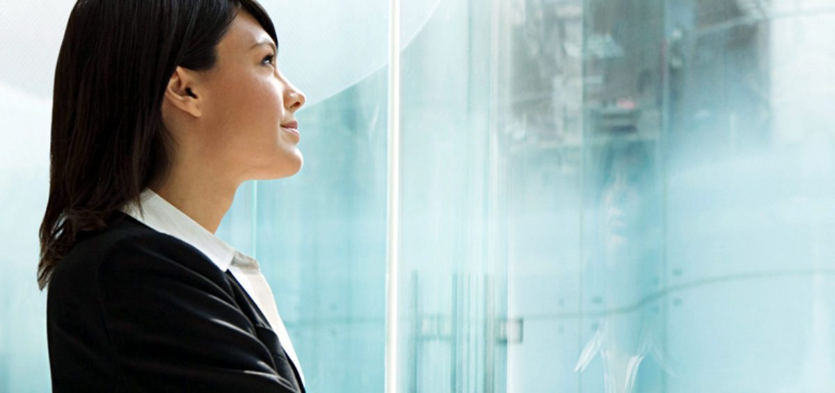 Corporate woman peering out full-length glass window, illustrating her successful personal brand