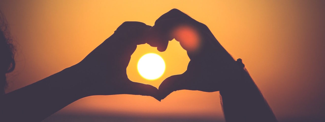 Hero background image of hand silhouette in heart shape against the sunset for organisational culture alignment services
