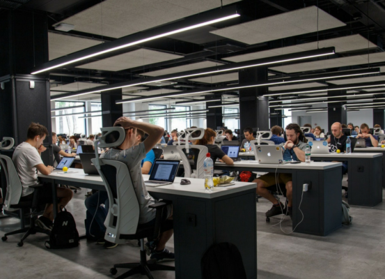 Open office with rows of workers on laptops